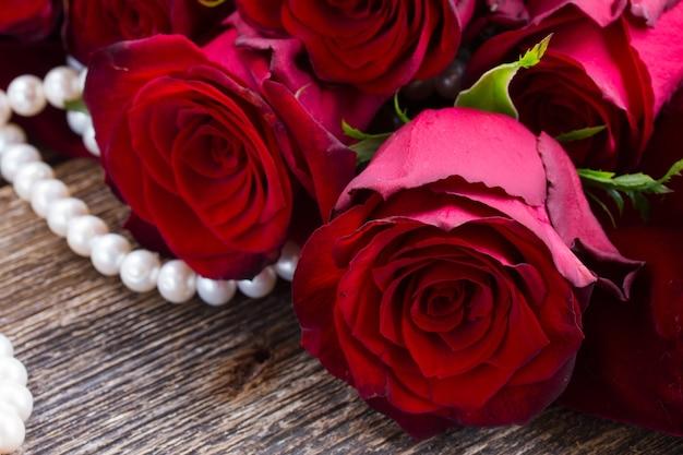 Свежие красные розы с жемчугом на деревянных фоне