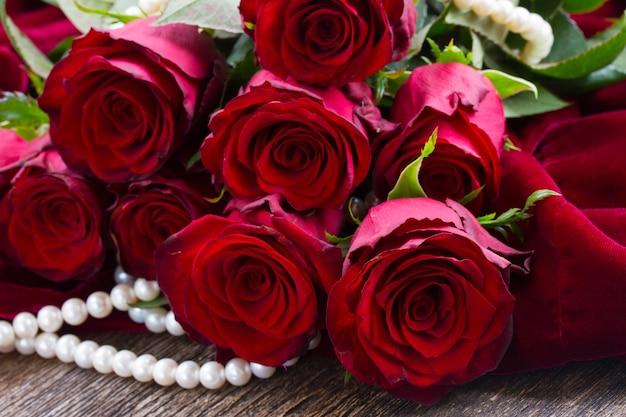 Свежие красные розы с бархатом на деревянных фоне
