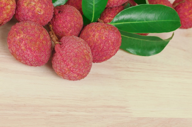 Fresh red skin lychee with leaves on wooden background with copy space.