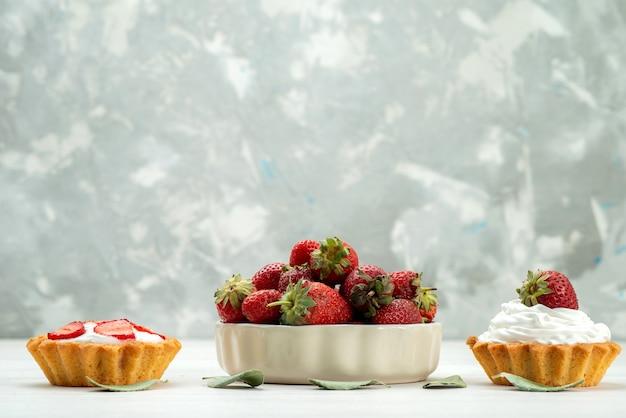 新鮮な赤いイチゴがまろやかでおいしいベリーがプレートの中にあり、ケーキが光を放っています