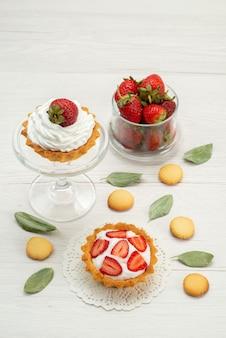 Свежая красная клубника, спелые и вкусные ягоды с тортами и печеньем на светлом столе