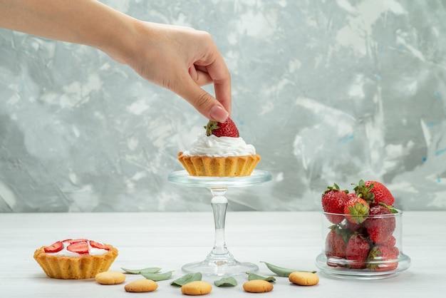 Свежая красная клубника, спелые и вкусные ягоды с тортами и печеньем на светло-сером столе