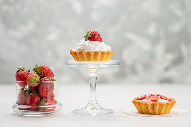 Свежая красная клубника, спелая и вкусные ягоды с тортами на светлом столе