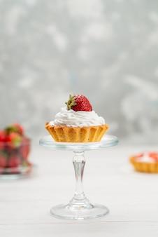 Свежая красная клубника спелая и вкусные ягоды с пирожными на свете