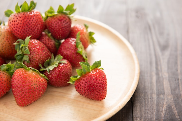 Fresh red strawberries on old wooden table