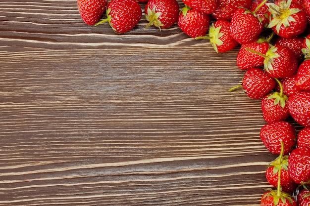 Свежая красная клубника на коричневом деревянном фоне