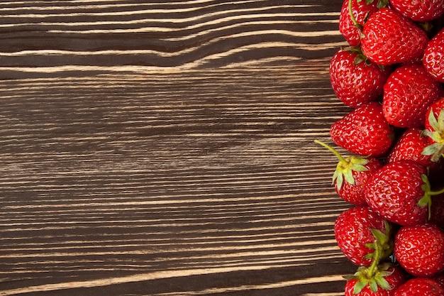 Свежая красная клубника на коричневом деревянном столе