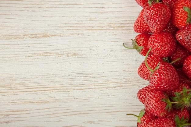 Свежая красная клубника на белом деревянном столе