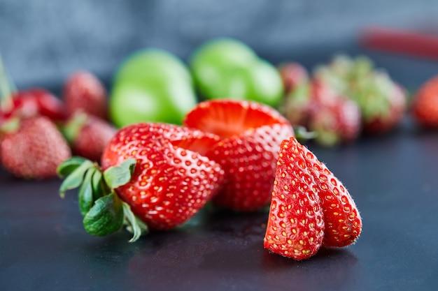 暗い表面に新鮮な赤いイチゴ