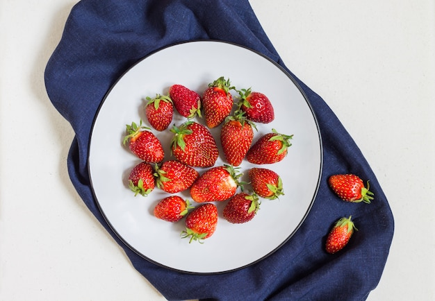 Fresh red strawberries on a white plate