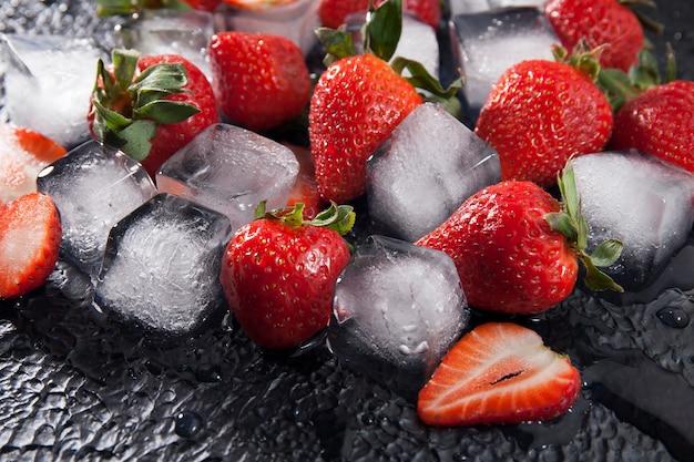 暗いテクスチャ背景に角氷と新鮮な赤いイチゴ