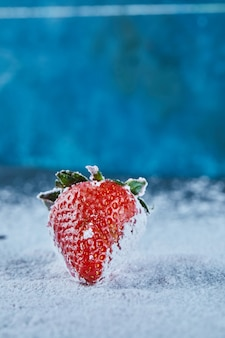 Fresh red strawberry on blue surface with powder