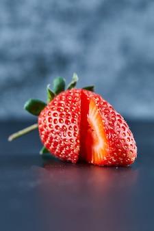 Fresh red strawberry slices on dark surface