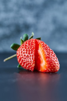 暗い表面に新鮮な赤いイチゴのスライス