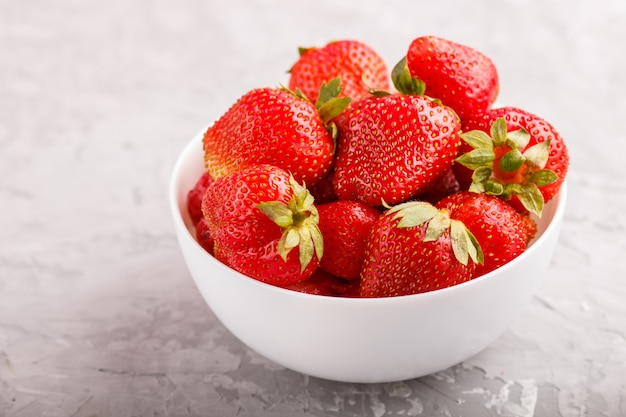 Fresh red strawberry in white bowl. side view.