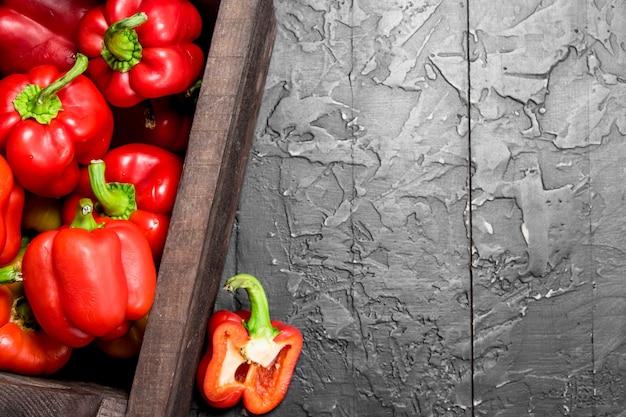 검은 시골 풍 테이블에 상자에 신선한 빨간 달콤한 고추 프리미엄 사진