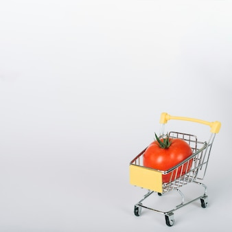 Fresh red tomato in shopping cart on white surface