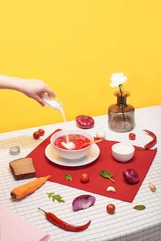 Свежий красный томатный суп в белой миске. натюрморт на желтом.