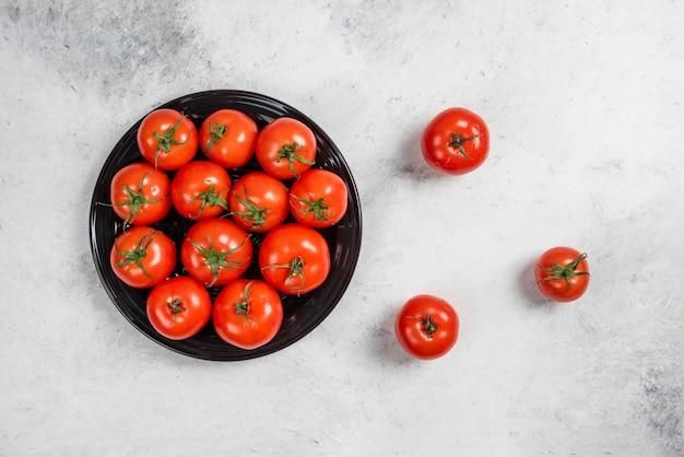 Pomodori rossi freschi su una banda nera.