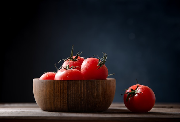 Fresh red tomatoes in bowl on wooden old table