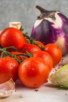 Свежие красные помидоры; зубчик чеснока; брюссельская капуста; баклажан на деревянной поверхности