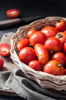 黒の背景にホイッカーバスケットの新鮮な赤いトマト。