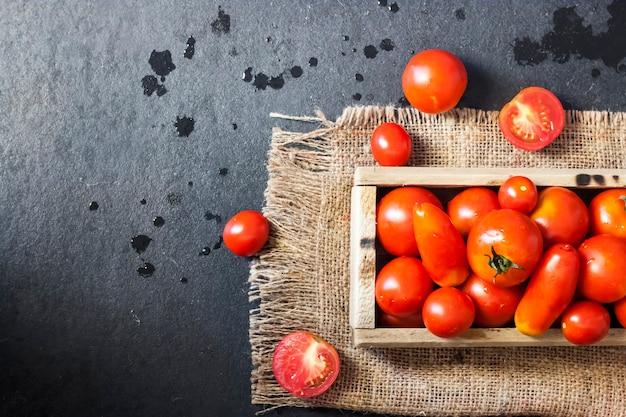 黒の背景に木製の箱で新鮮な赤いトマト。フラットレイ、上面図、コピースペース