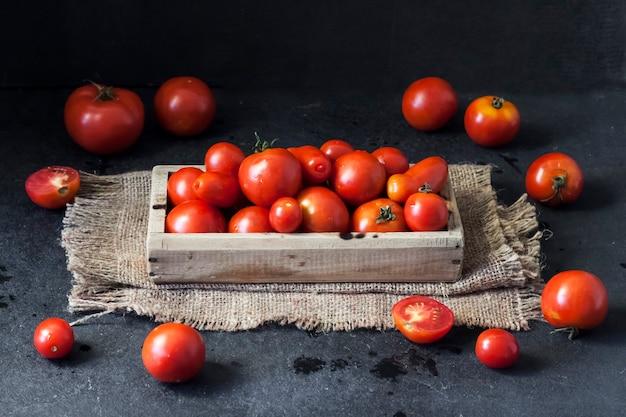 黒の背景に木製の箱で新鮮な赤いトマト。フラットレイ、上面図