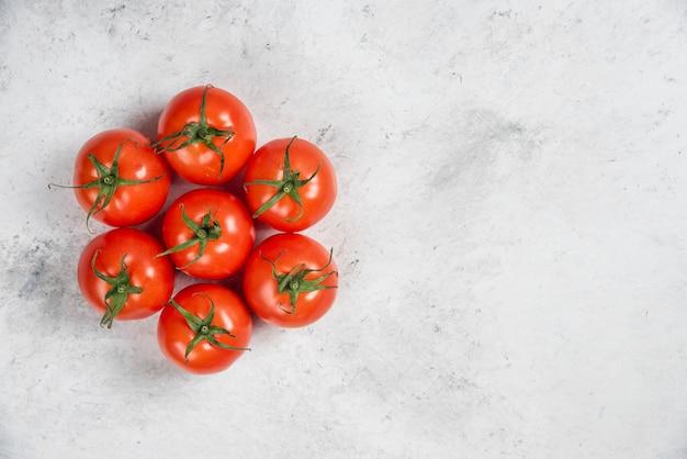 Pomodori rossi freschi su uno sfondo di marmo