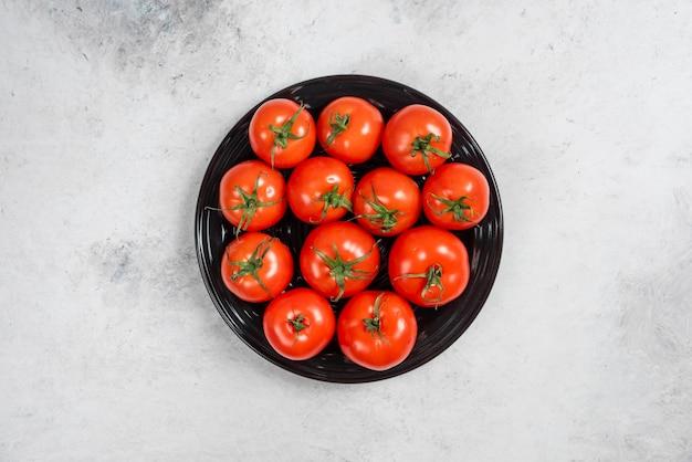 黒いプレートに新鮮な赤いトマト。