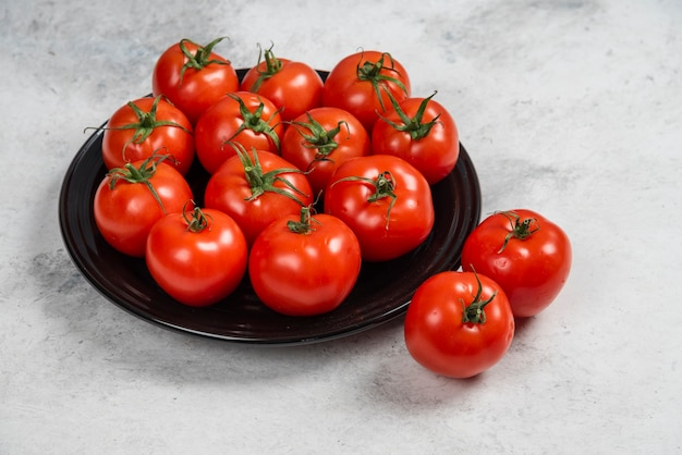 검정 잉크 판에 신선한 빨간 토마토입니다.