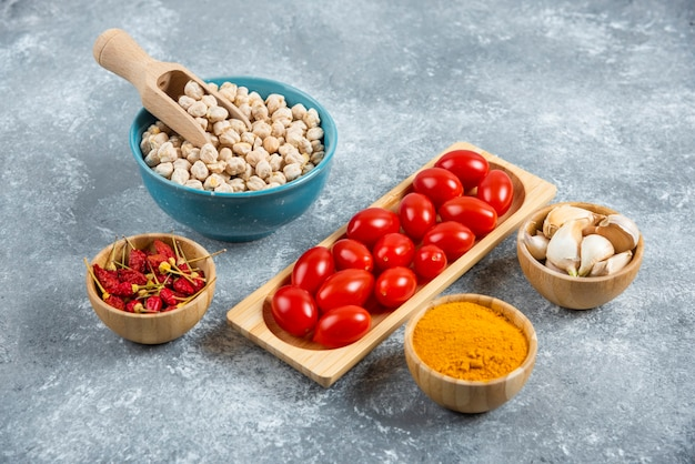 Fresh red tomatoes and raw chickpeas on marble background.