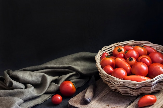 Fresh red tomatoes in whicker basket on black background copy space