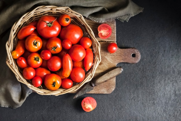Fresh red tomatoes in whicker basket on black background flat lay top view copy space