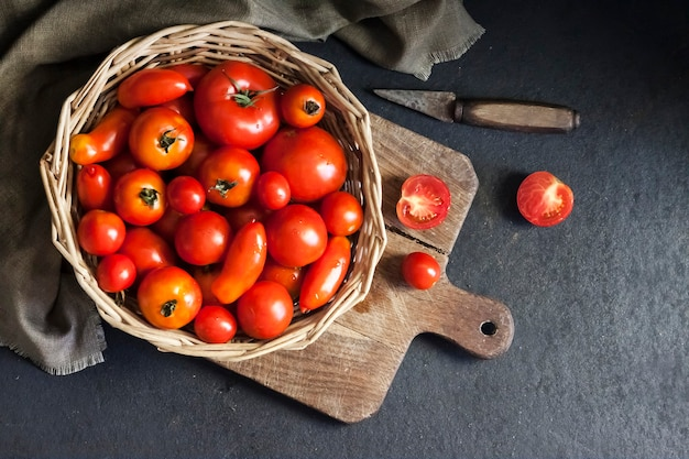 Fresh red tomatoes in whicker basket on black background. flat lay, top view