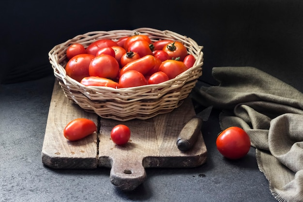 Fresh red tomatoes in whicker basket on black background