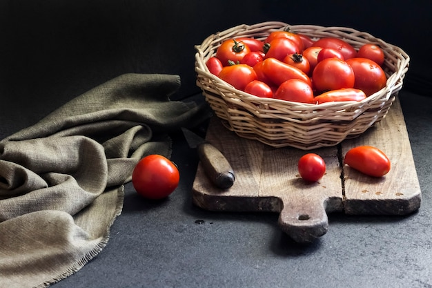 Fresh red tomatoes in whicker basket on black background.
