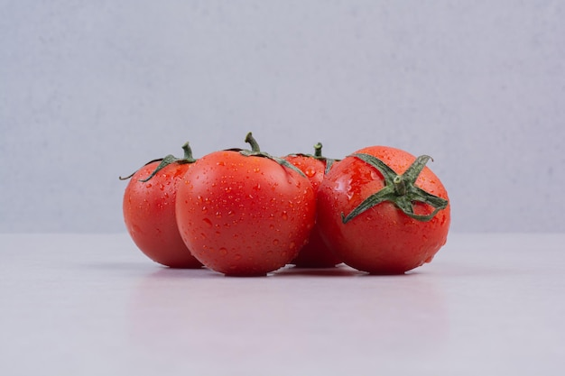 Pomodori rossi freschi sulla tavola bianca.