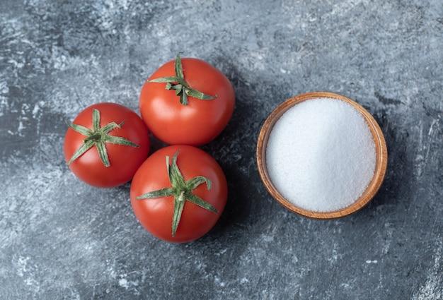 Pomodori rossi freschi con una ciotola di legno piena di sale.