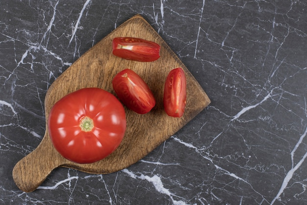 Fresh red tomatoes on wooden board.
