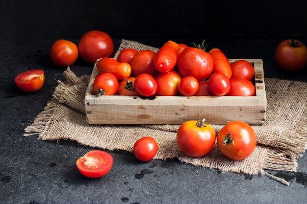 Fresh red tomatoes in wooden box on black background.