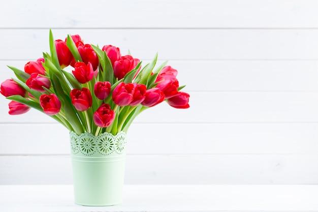 Букет свежих красных тюльпанов на полке перед деревянной стеной.