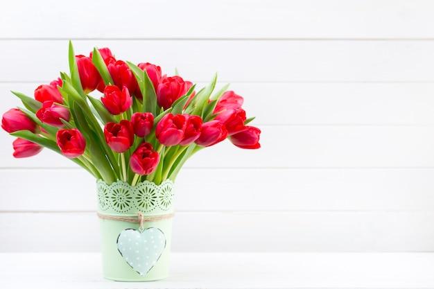 木製の壁の前の棚に新鮮な赤いチューリップの花の花束。