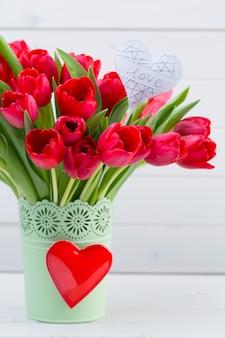 木製の壁の前の棚に新鮮な赤いチューリップの花の花束