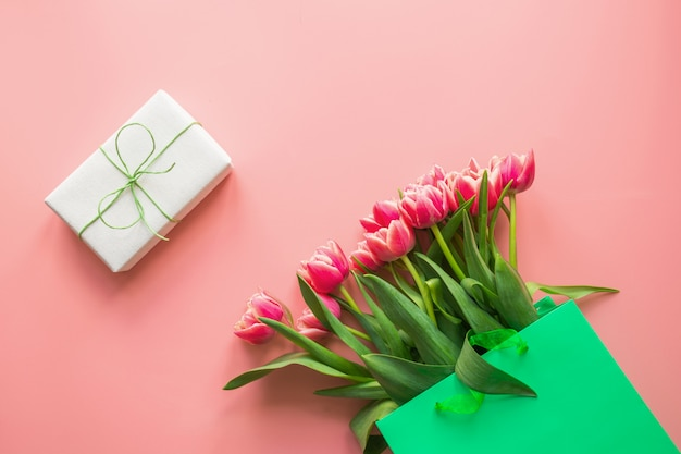 Fresh red tulip flowers in green paper bag on pink. spring. mother day.