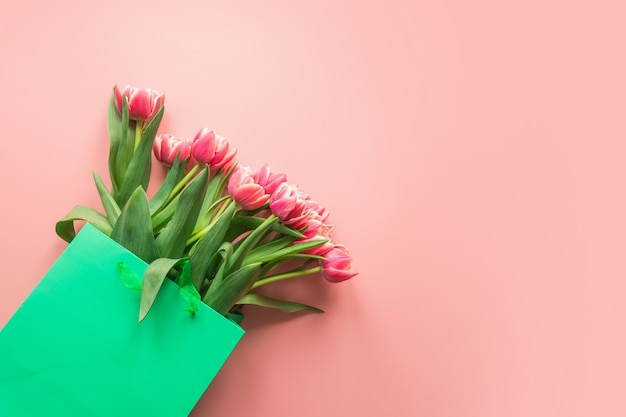 Fresh red tulip flowers in green paper bag on pink. spring.
