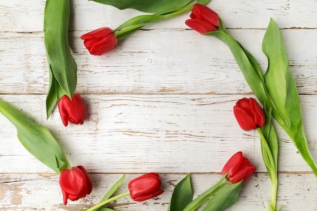 Свежие красные тюльпаны на деревянном столе