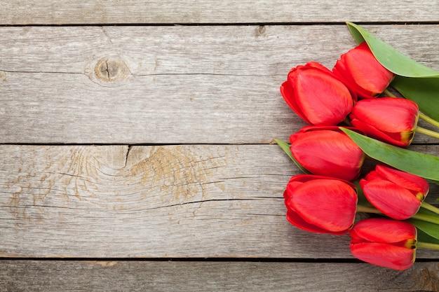 Букет из свежих красных тюльпанов на фоне деревянного стола с копией пространства