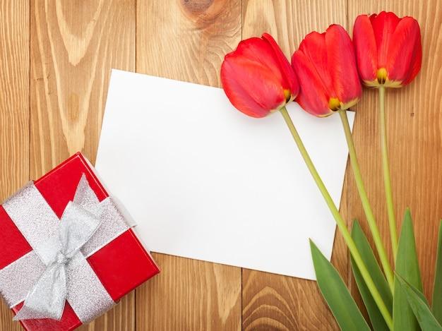 Свежие красные тюльпаны с подарочной коробкой и поздравительной открыткой на деревянном фоне