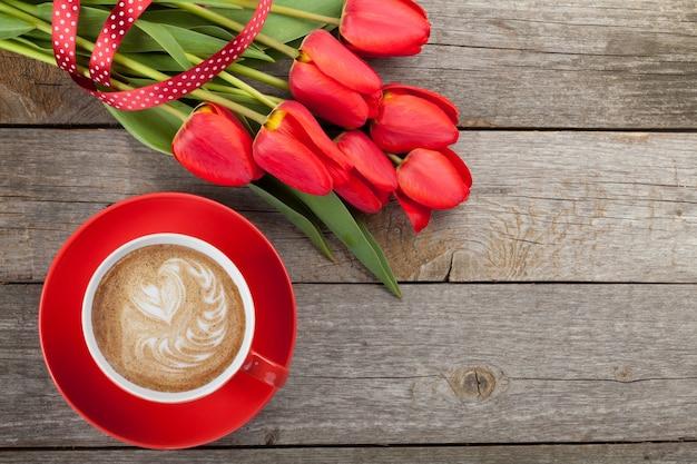 Свежие красные тюльпаны с лентой и кофейной чашкой в форме сердца на деревянном фоне с копией пространства